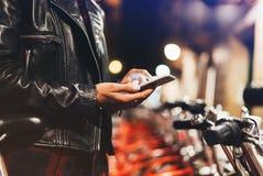 Маленькая девочка в черной кожаной куртке используя smartphone на свете bokeh зарева освещенности фона в городе ночи атмосферичес Стоковое фото RF