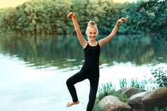 Маленькая девочка в черной футболке и гетры делая физические упражнения стоковое изображение