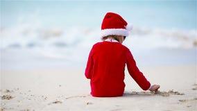 Маленькая девочка в шляпе рождества на белом пляже во время каникул Xmas видеоматериал