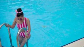 Маленькая девочка в striped розовом купальнике спускает в бассейн сток-видео