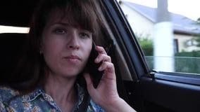 Маленькая девочка говорит на телефоне и управляет автомобилем на дороге города с открытым окном видеоматериал