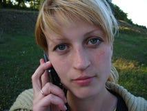 Маленькая девочка говоря на телефоне на предпосылке природы Стоковые Изображения