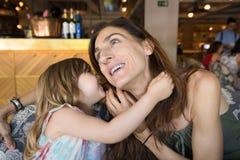 Маленькая девочка говоря, что секрет в ухе был матерью в ресторане Стоковое Изображение