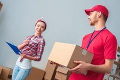 Маленькая девочка двигая к новому месту стоя проверяющ заказ от коробки удерживания работника доставляющего покупки на дом стоковые фото