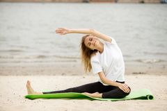 Маленькая девочка делает протягивать на циновке йоги на песчаном пляже на теплый день стоковое фото rf