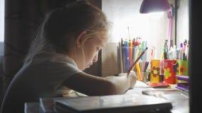 Маленькая девочка делает свою домашнюю работу на на таблице под светом лампы творческое хобби маленькой принцессы образ жизни  акции видеоматериалы