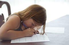 Маленькая девочка делая домашнюю работу на кухонном стол столе Стоковые Фотографии RF