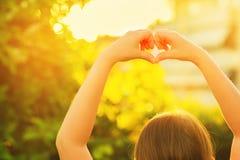 Маленькая девочка делая знак сердца с ее руками Стоковые Фотографии RF