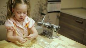 Маленькая девочка делая макаронные изделия в кухне акции видеоматериалы