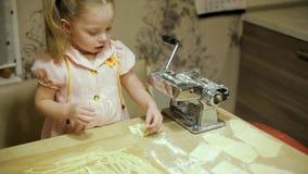 Маленькая девочка делая макаронные изделия в кухне сток-видео