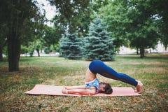 Маленькая девочка делая тренировку йоги outdoors стоковое фото rf