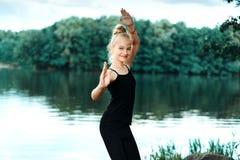 Маленькая девочка делая фитнес, pilates на речном береге стоковое фото