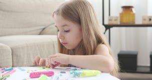 Маленькая девочка делая формы используя красочный пластилин акции видеоматериалы