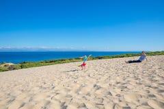 Маленькая девочка делая handstand на песке рядом с матерью стоковые изображения