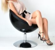 Маленькая девочка дела сидя на вращая стуле в белом платье и пятках Стоковые Изображения