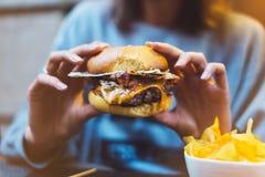 Маленькая девочка держа в женщине вручает бургер фаст-фуда, американские нездоровые калории еды на предпосылке, модель-макете с к стоковое фото