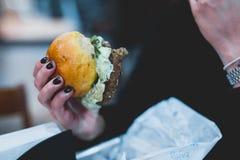 Маленькая девочка держа в женщине вручает бургер фаст-фуда стоковые изображения rf