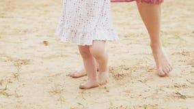 Маленькая девочка держа ее руку ` s матери и уча идти сток-видео