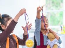 Маленькая девочка держа золотую медаль для награды студента стоковые изображения
