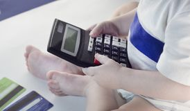 Маленькая девочка держа калькулятор и кредитные карточки, конец-вверх, белый стоковые фотографии rf
