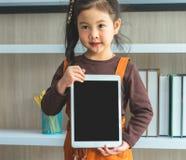 Маленькая девочка держа пустую насмешку планшета вверх в классе стоковое изображение rf