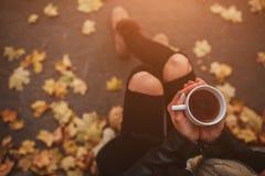 Маленькая девочка держа чашку горячего питья и усмехаясь на предпосылке молодой женщины леса осени привлекательной внутри Стоковые Фото