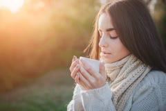 Маленькая девочка держа чашку горячего питья и усмехаясь на предпосылке молодой женщины леса осени привлекательной внутри Стоковые Изображения