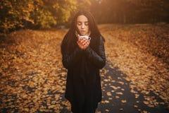 Маленькая девочка держа чашку горячего питья и усмехаясь на предпосылке молодой женщины леса осени привлекательной внутри Стоковое Изображение RF