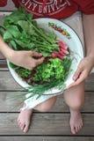 Маленькая девочка держа шар с первым сбором редисок, салата и луков стоковая фотография rf