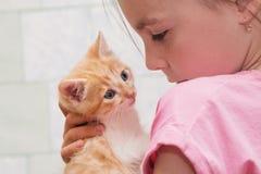 Маленькая девочка держит котенка в ее оружиях и объятиях стоковая фотография rf