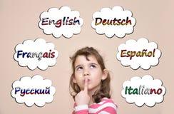 Маленькая девочка думая которые языки для того чтобы выучить Стоковая Фотография RF
