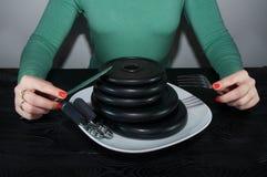 Маленькая девочка есть диски литого железа любит блинчики на белой таблице черноты плиты Стоковое Изображение
