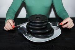 Маленькая девочка есть диски литого железа любит блинчики на белой таблице черноты плиты Стоковые Фото
