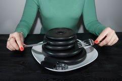 Маленькая девочка есть диски литого железа любит блинчики на белой таблице черноты плиты Стоковое Фото