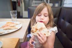 Маленькая девочка есть пиццу с рукой в ресторане Стоковое Изображение RF