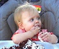 Маленькая девочка есть шоколадный торт стоковые фотографии rf