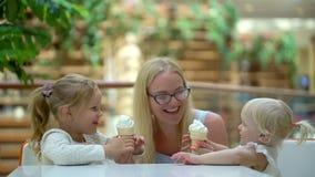 Маленькая девочка ест мороженое рожок в большом торговом центре Семья ест мороженое в моле семья счастливая мило сток-видео