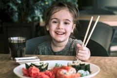 Маленькая девочка ест суши Стоковые Изображения
