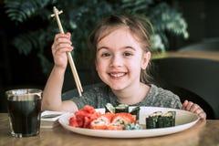 Маленькая девочка ест суши Стоковая Фотография