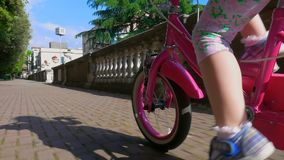 Маленькая девочка ехать велосипед на солнечный день сток-видео