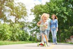 Маленькая девочка ехать самокат на парке Стоковое фото RF