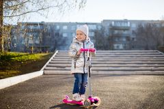 Маленькая девочка ехать скутер в парке на солнечный весенний день Активный отдых и на открытом воздухе спорт для детей стоковое фото