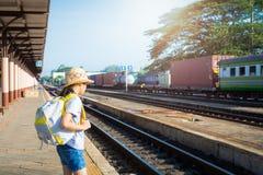 Маленькая девочка ждать поезд на железнодорожном вокзале стоковая фотография rf
