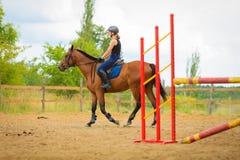 Маленькая девочка жокея делая лошадь скача через барьер Стоковые Фотографии RF