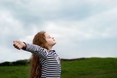 Маленькая девочка закрыла ее глаза и дышать с свежим дуя воздухом стоковая фотография rf