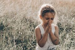 Маленькая девочка закрыла ее глаза моля на заходе солнца Руки сложили в концепции молитве для веры, духовности и вероисповедания  стоковое изображение rf