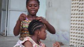 Маленькая девочка заплетает ее маленькую сестру сидя перед ей видеоматериал