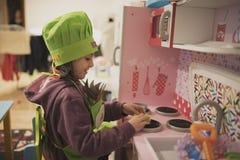 Маленькая девочка играет в кухне игрушки стоковая фотография