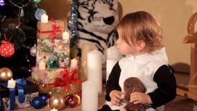 Маленькая девочка играет около рождественской елки с подарком ` s Нового Года видеоматериал