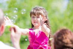Маленькая девочка играет с пузырями мыла стоковое изображение